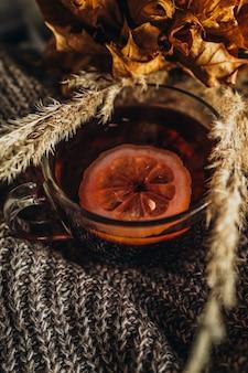 温かみのあるニット生地にレモンと乾燥した植物を入れた熱いお茶のカップ秋の居心地の良い家の静物