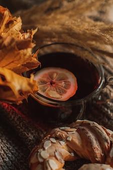 ニット生地にレモンとアーモンドのペストリーを添えたホットティー一杯秋の居心地の良い静物
