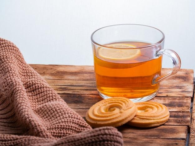 Чашка горячего чая с лимоном на вязаном свитере