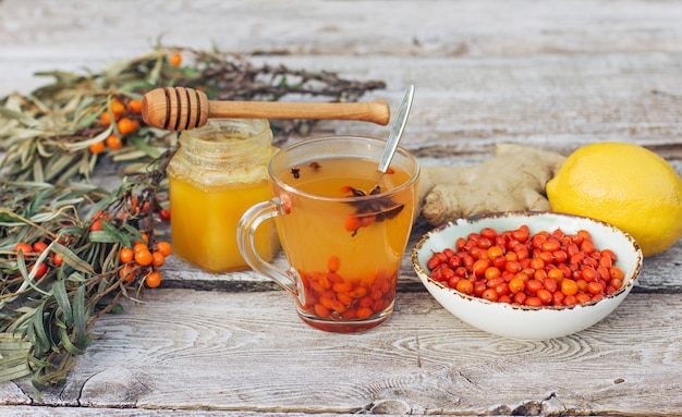 뜨거운 비타민 씨 벅톤 차, 레몬, 생강 한 컵이 오래된 나무 테이블에 있습니다. 독감철 감기예방키트와 코로나19 한약재