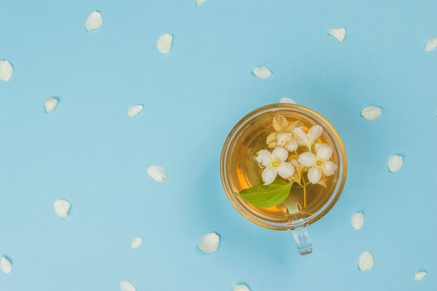 花びらと青い背景にジャスミン茶のカップ。健康に良い爽快なドリンク。