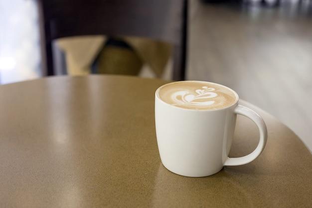 Чашка позднего искусства кофе на столике в кафе