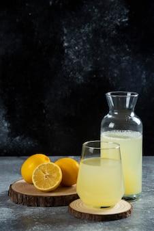 나무 보드에 레몬 주스 한잔.
