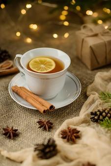 クリスマスの飾りを背景に、選択的な焦点で撮影されたレモンティーのカップ。