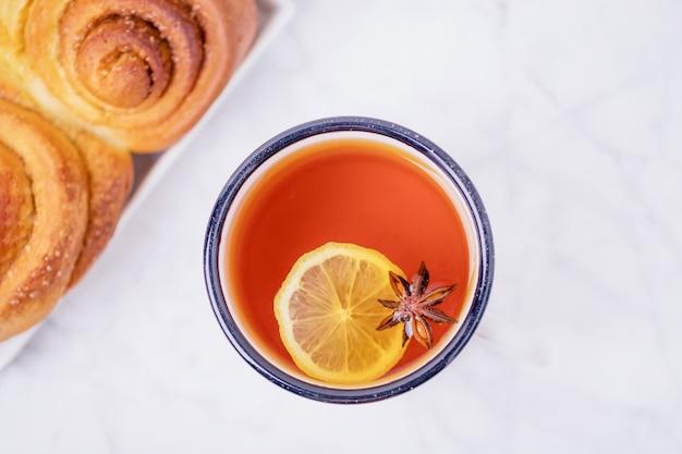 Чашка лимонного чая с звездочкой аниса и домашней корицей, булочки с корицей на белом мраморном фоне