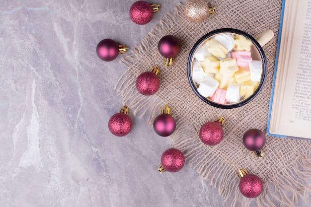 赤いクリスマスツリーのボールが周りにあるマシュマロドリンクのカップ