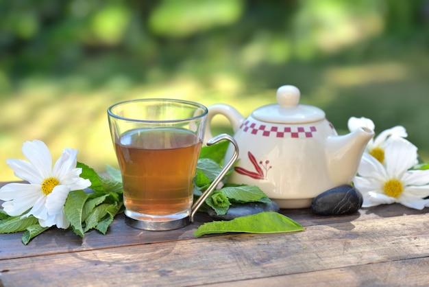 Чашка мятного чая и чайник на деревянном столе в саду среди свежих листьев и белых цветов