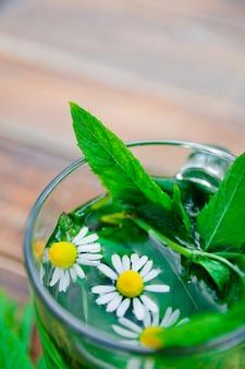 木製の背景にカモミールとミントティーのカップ。テーブルにカモミールと新鮮なミントの葉とハーブティー。