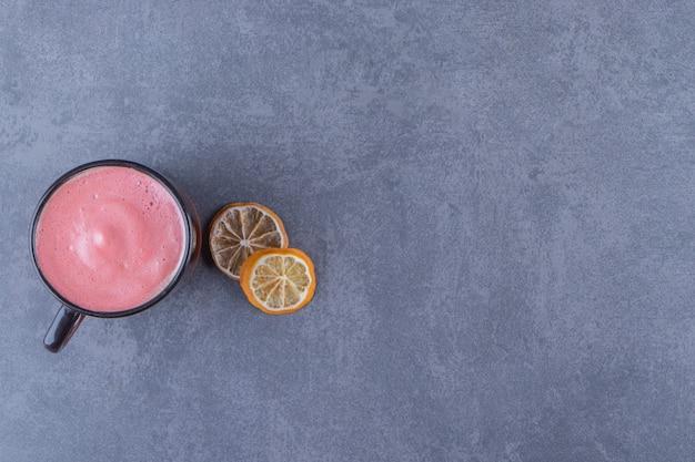 青い背景に、レモンスライスの横にあるピンクのコーヒーのカップ。高品質の写真