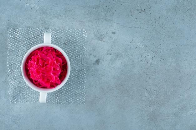 Чашка красной квашеной квашеной капусты на синем столе.