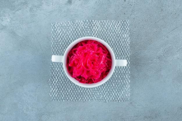 파란색 테이블에 붉은 발효 소금에 절인 양배추 한 컵.