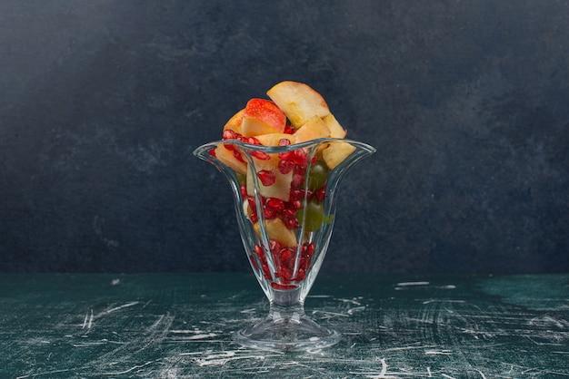 大理石の表面にリンゴのスライスのカップ