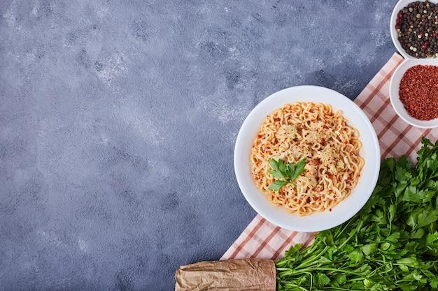 Чашка спагетти со специями вокруг.