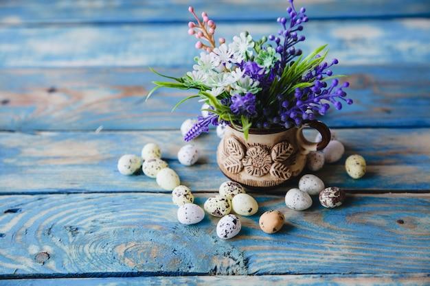春の紫色の花のカップと古い、すり切れた青いテーブルの上にウズラの卵が散らばっています。