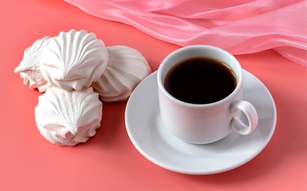 Чашка крепкого ароматного кофе и нежный белый ванильный зефир на розовой поверхности