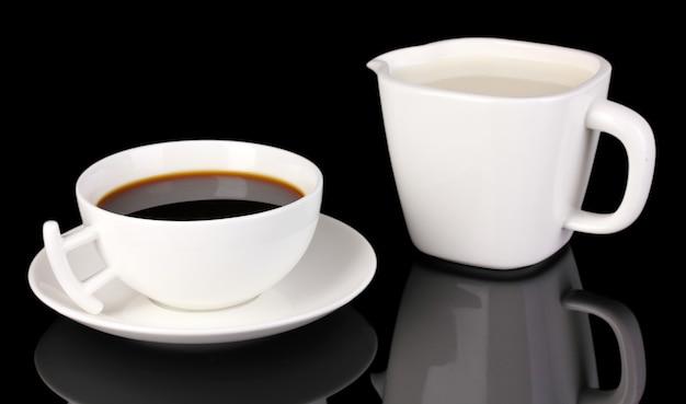 黒で分離された濃いコーヒーと甘いクリームのカップ