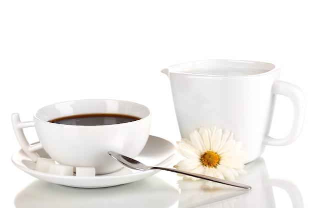 白で分離された濃いコーヒーと甘いクリームのカップ