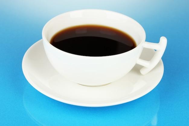 青い背景に濃いコーヒーのカップ