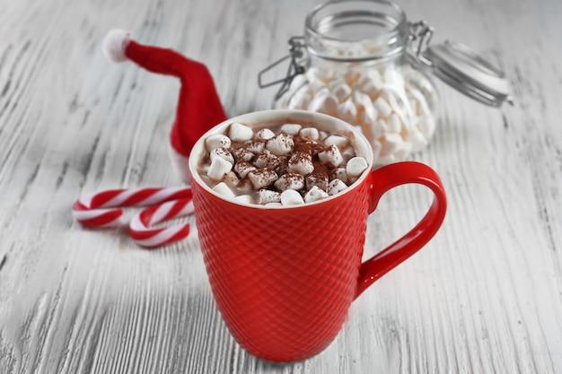 Чашка вкусного какао и зефира на белом деревянном фоне