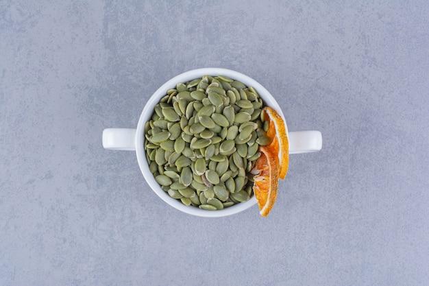 Чашка вкусных тыквенных семечек с сушеным лимоном на мраморе.