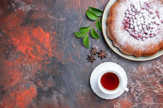Чашка чая чашка черного чая торт с ягодами звездчатого аниса и листьями