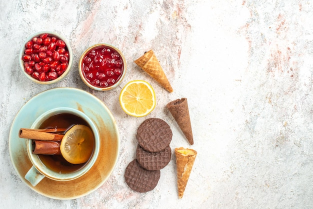 Чашка чая чашка чая палочки корицы лимон чаша ягод печенье