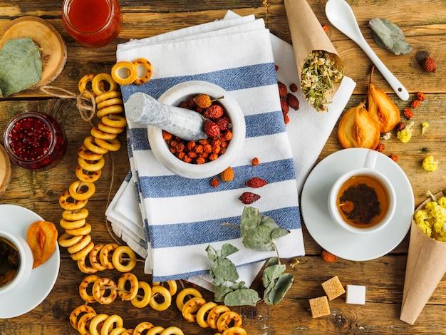 Чашка чая и синее полотенце на старой деревянной поверхности. травы и сладости.