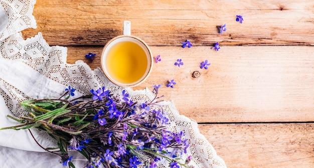 一杯のお茶と木製の背景に青い花の花束。長いバナー