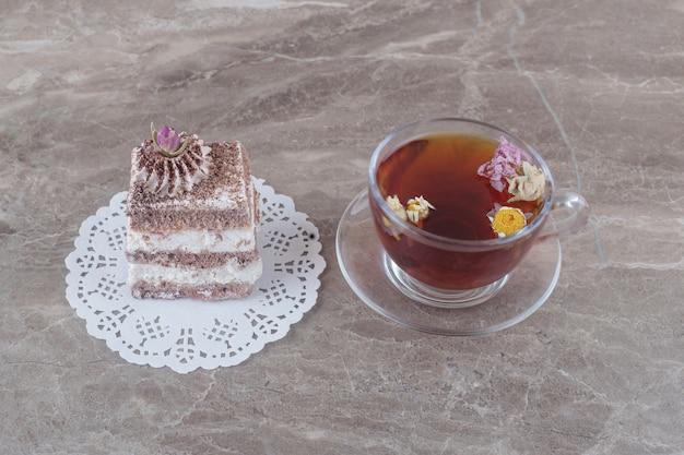 Чашка чая и кусок торта на салфетке на мраморе
