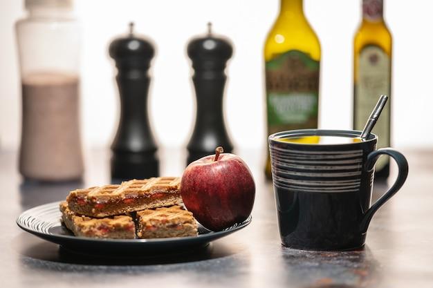 Чашка чая и тарелка с печеньем и яблоком, стоящие на столе