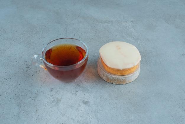 차 한잔과 대리석 배경에 작은 흰색 초콜릿 케이크. 고품질 사진
