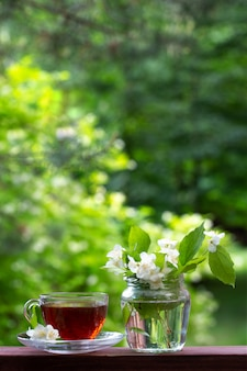 Чашка чая и ваза с веточками жасмина.