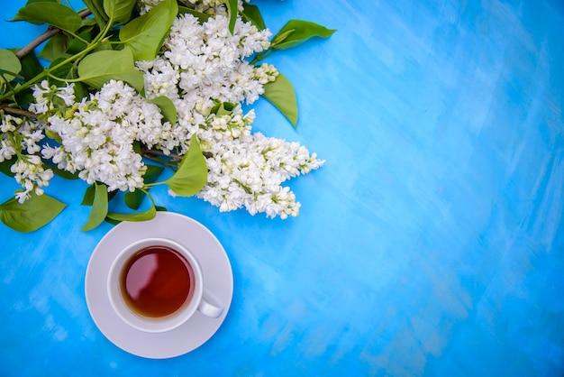 Чашка чая и ветки персидской махровой белой сирени на синем фоне, вид сверху