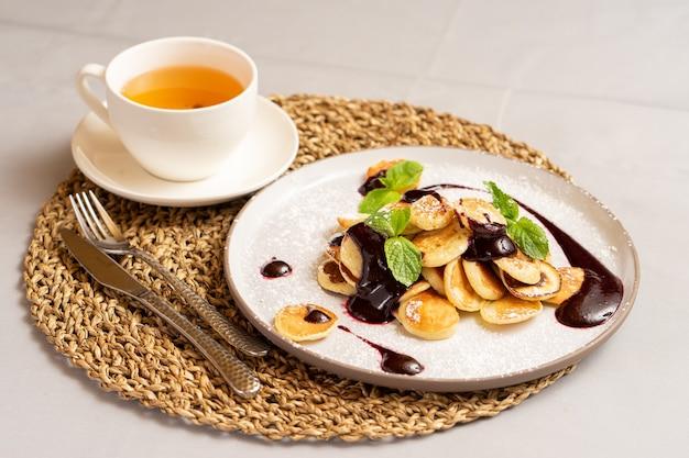 Чашка чая и мини-блины с ягодным вареньем и мятой, посыпанные сахарной пудрой.