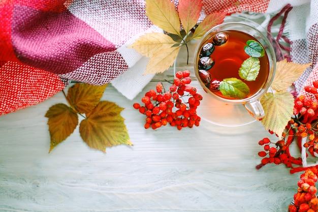 一杯のお茶と木製のテーブルのナナカマドの果実。秋の静物。
