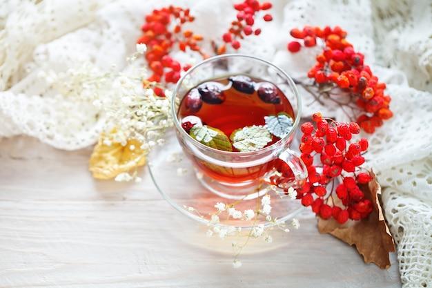 나무 테이블에 차와 마가 목 열매의 컵. 가을 정물.