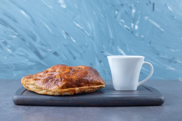 Чашка чая и сладкий пирог на деревянном подносе на мраморном столе.