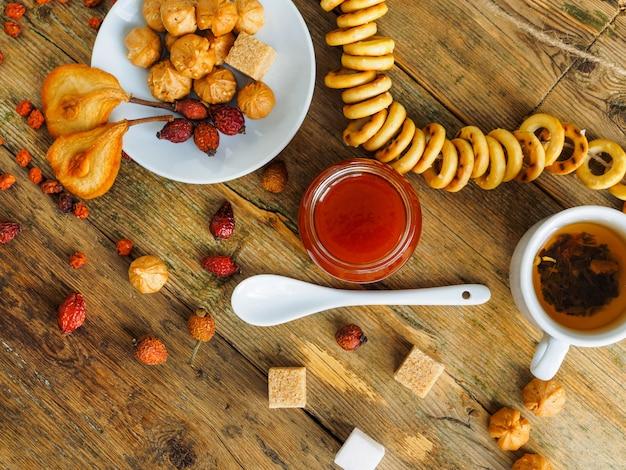Чашка чая и сладостей на деревянном столе. уютная атмосфера.