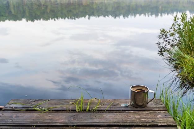 숲의 호수에서 차 한 잔. 캠핑, 트레킹, 하이킹 컨셉입니다. 야외 활동 스톡 사진.