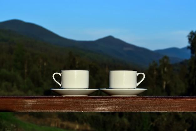 ホテルのバルコニーのポーチに立つ紅茶、コーヒーのカップ