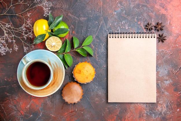 ノートブックの横にあるお茶のカップケーキのカップティーレモンのスターアニスのカップ