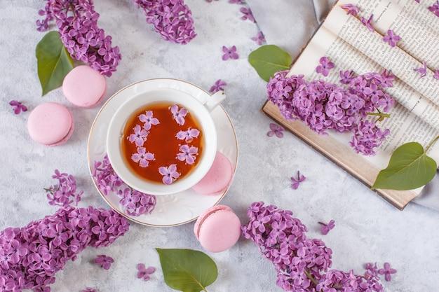Чашка чая, безе, ветки цветущей сирени и старинная книга.