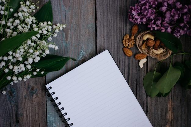 차, 견과류, 라일락 컵 및 나무 배경에 노트북