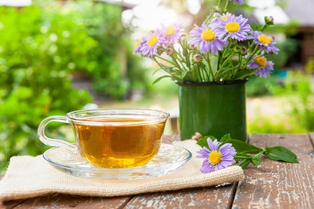 자연을 배경으로 나무 탁자에 있는 차 한 잔