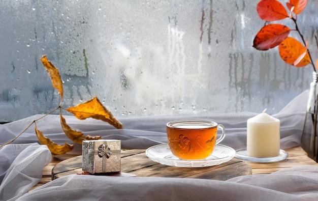 秋の雨滴のある窓にお茶を一杯。温かい飲み物とお手入れが必要な季節。