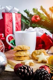 お祝いの装飾、クリスマスのクッキーと新年のテーブルにお茶やコーヒーのカップ