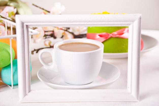 一杯のお茶、小さな春のケーキ、花さくら、イースターの日のためのカラフルな卵。春のコンセプトです。