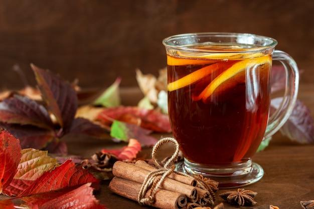 Чашка чая стоит на столе, усыпанном осенними листьями