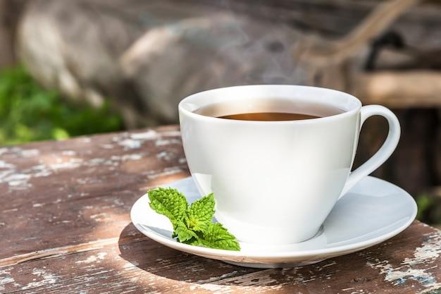 오래된 나무 판자에 녹색 잎이 달린 차 한 잔과 자연과 시골의 배경.