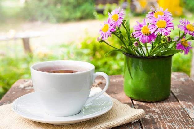 자연과 시골의 배경에 꽃다발과 함께 오래된 나무 판자에 녹색 잎을 얹은 차 한 잔.